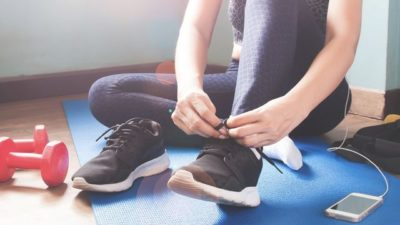 young woman tying shoe on sports mat royalty free image 1587302457
